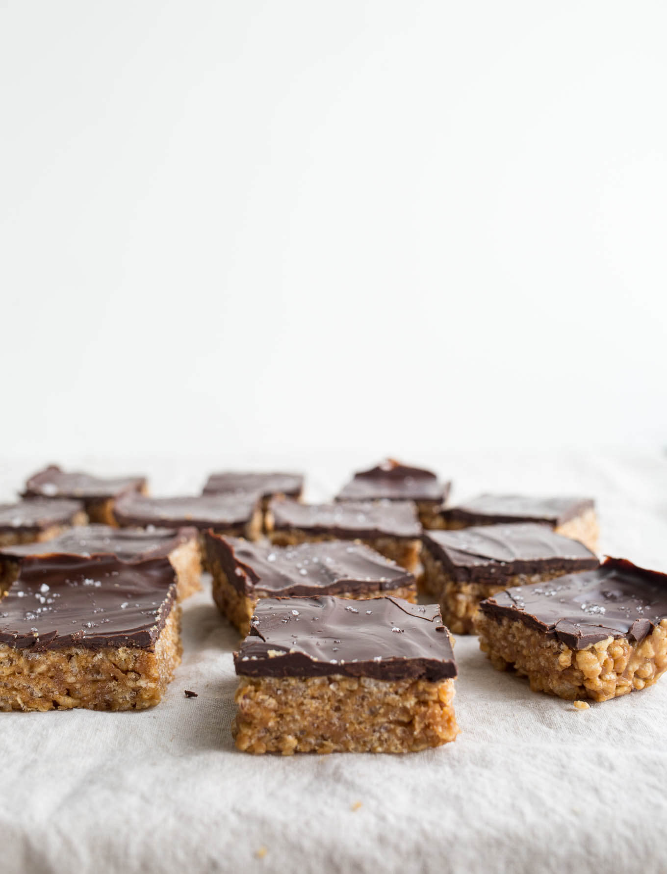 Peanut Butter Maple Scotcheroos are a healthier take on the classic treat. Made with brown rice cereal, peanut butter, maple syrup, and dairy-free chocolate. Gluten-free, vegan, refined sugar-free.