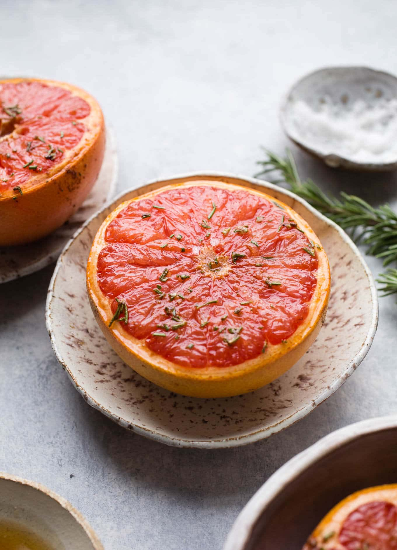 Broiled grapefruit with maple syrup, rosemary, and sea salt make for a delicious sweet and salty breakfast or brunch option. Gluten-free, vegan.