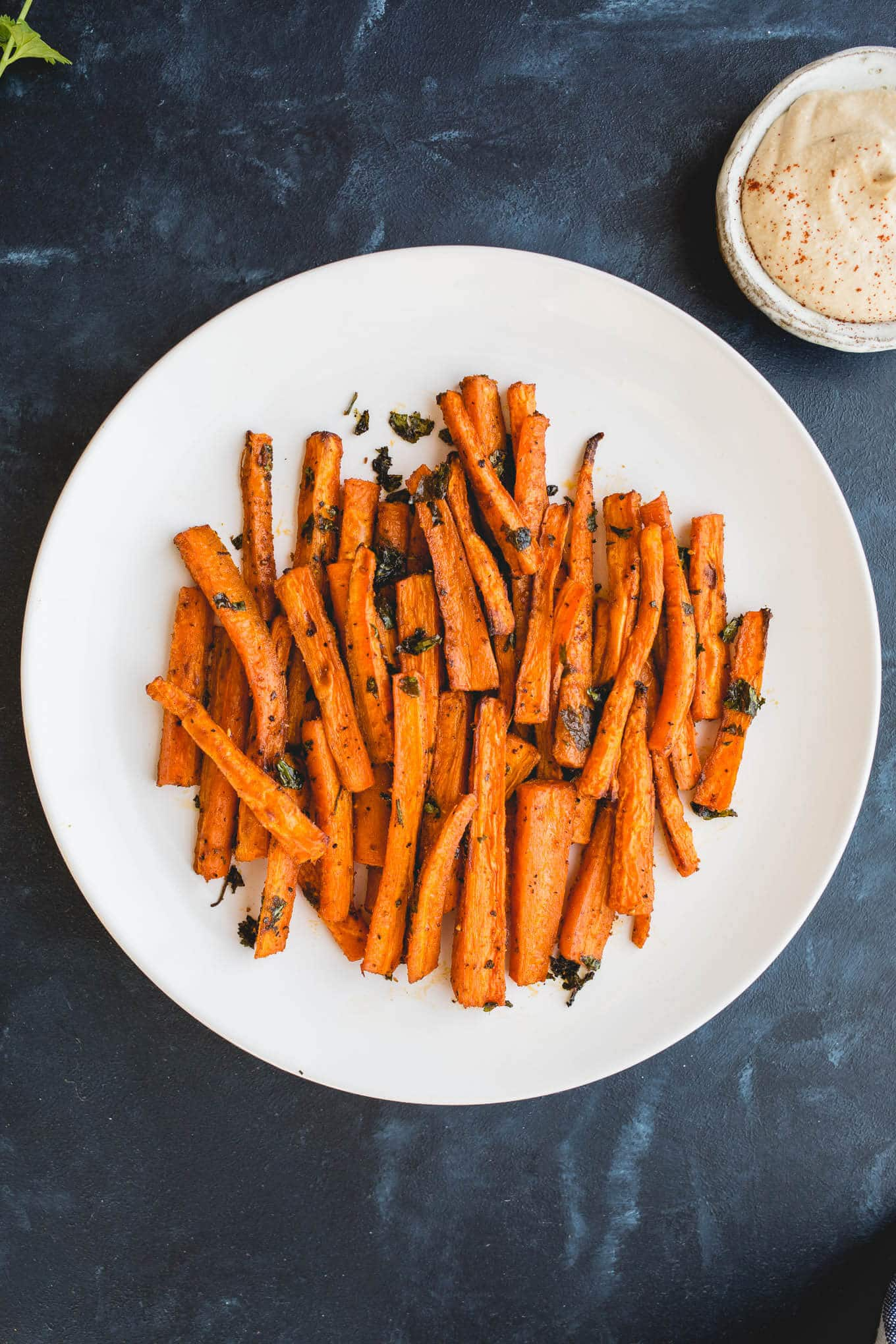 Oven Baked Carrot Fries tossed with olive oil, paprika, garlic powder, salt, pepper, and parsley, for a deliciously healthy snack recipe. Gluten-free, vegan.