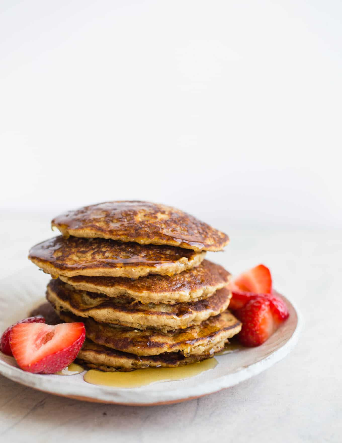 Gluten-free Vegan Oat Flour Pancakes made with whole grain gluten-free oats, white rice flour, applesauce, and non-dairy buttermilk, for a light and tender crumb. An oat flour pancake recipe made without eggs or bananas. Easy and delicious!