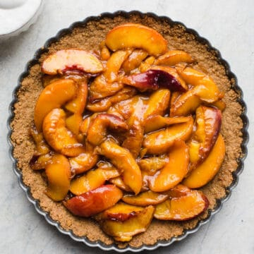 Roasted Peach Tart made with a gluten-free graham cracker crust, peaches roasted with coconut sugar, and served with a ginger-flavored coconut whipped cream. Simple and delicious! Gluten-free, vegan, refined sugar-free.
