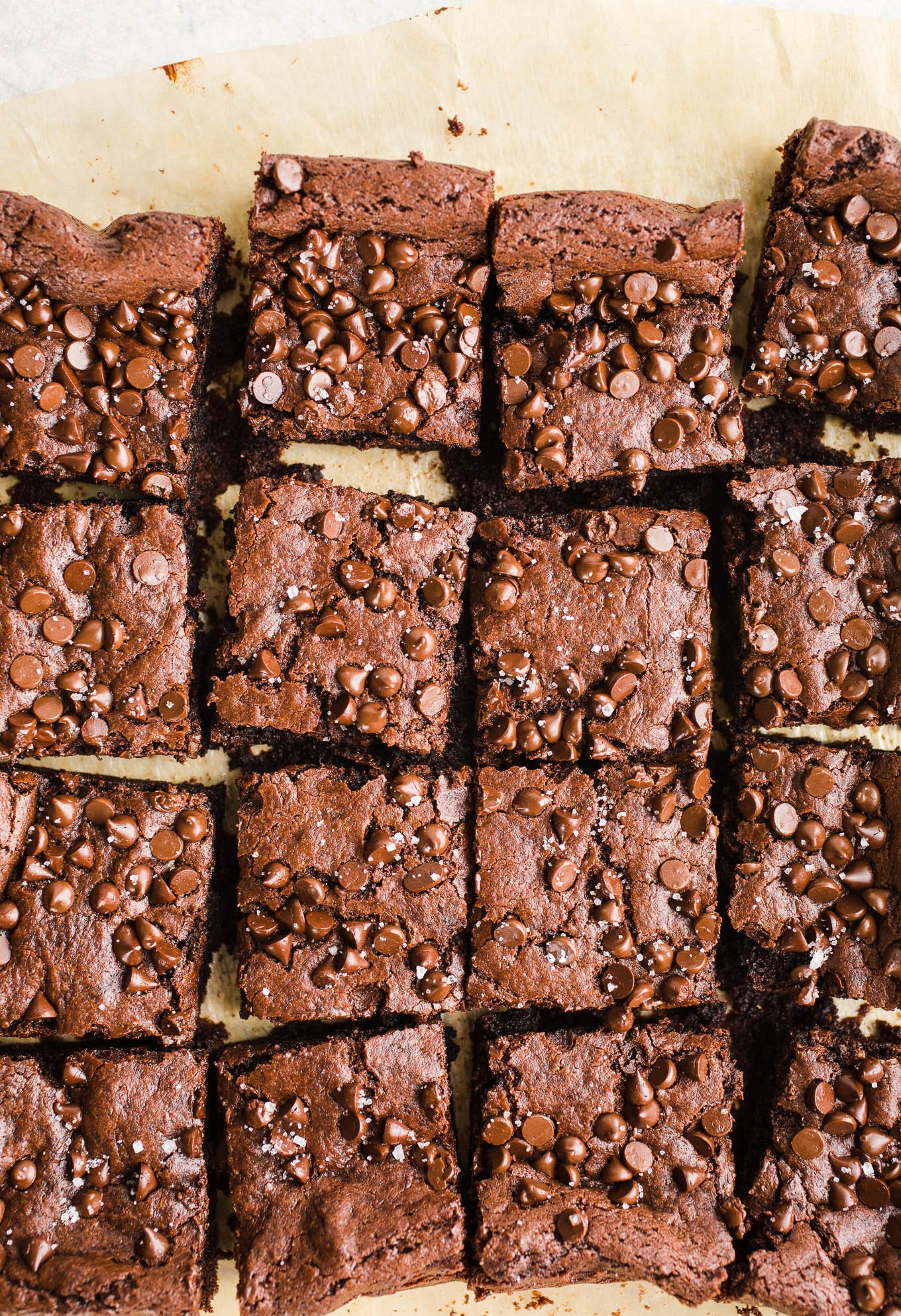 Vegan Tahini Brownies made with rich cocoa powder, tahini, maple syrup, chocolate chips, and topped with sea salt. Gluten-free.