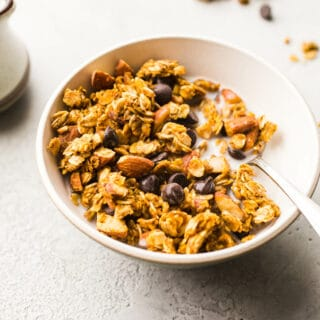 This easy pumpkin granola recipe is made with healthy gluten-free oats, almonds, pumpkin puree, and chocolate chips! Vegan.