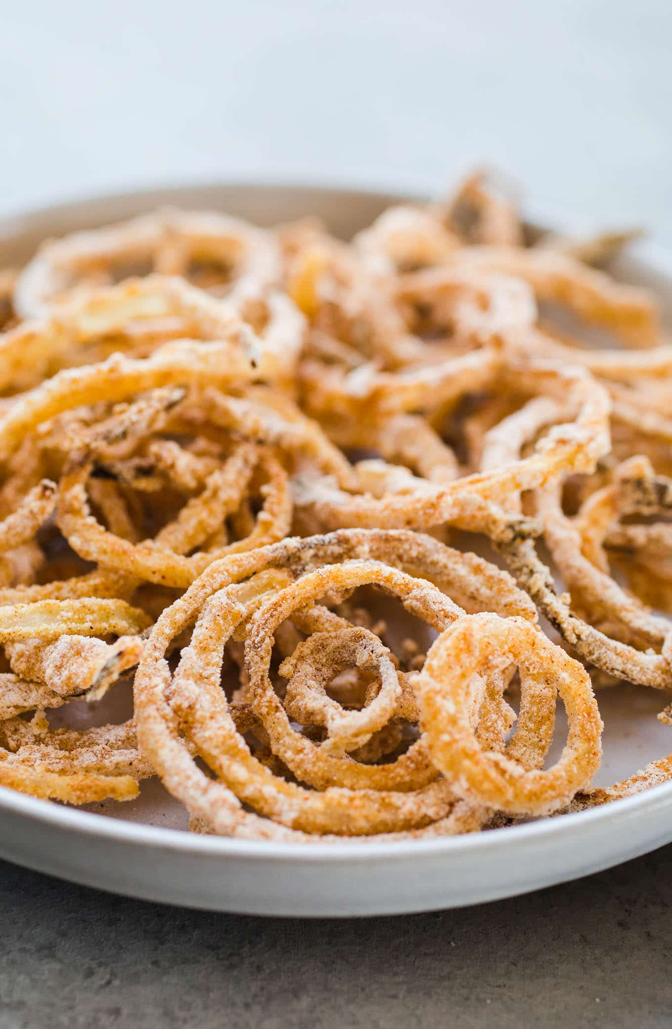 A Gluten-Free Onion Strings recipe that is baked, not fried. Made with white rice flour, dairy-free buttermilk, and spices, these won't last long!