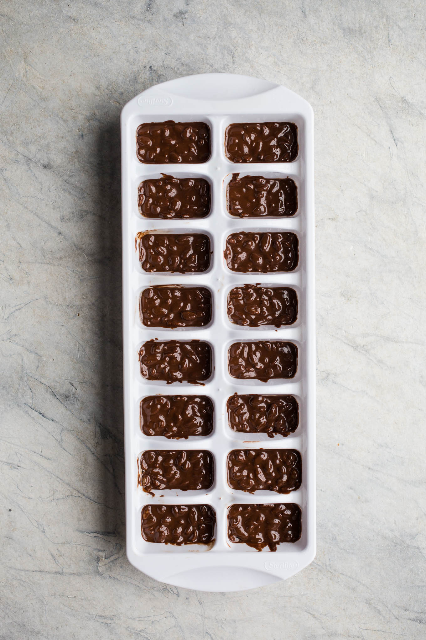 Homemade Mini Crunch Bars made with dairy-free chocolate, gluten-free rice cereal, and coconut oil. Use a standard ice cube tray to make these individual serving chocolate crunch treats!