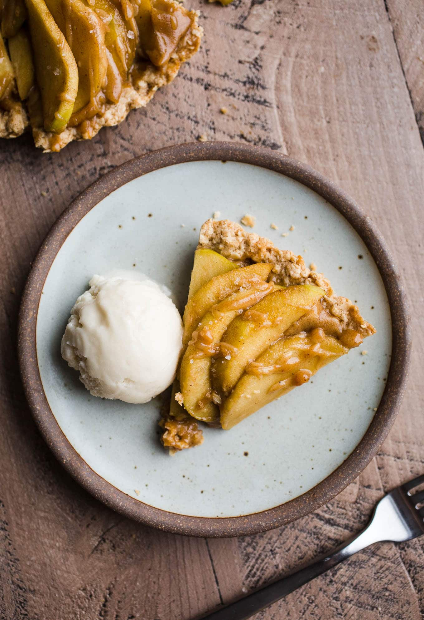 Gluten-Free Apple Tart with Oatmeal Cookie Crust is an easy dessert recipe made with an oat flour crust, a layer of date caramel, and topped with cinnamon apples. Prepare the crust and date caramel ahead of time for easier assembly. Vegan
