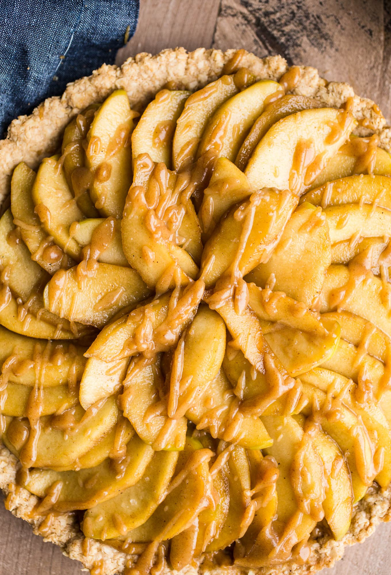 Gluten-Free Apple Tart with Oatmeal Cookie Crust is an easy dessert recipe made with an oat flour crust, a layer of date caramel, and topped with cinnamon apples. Prepare the crust and date caramel ahead of time for easier assembly.Vegan