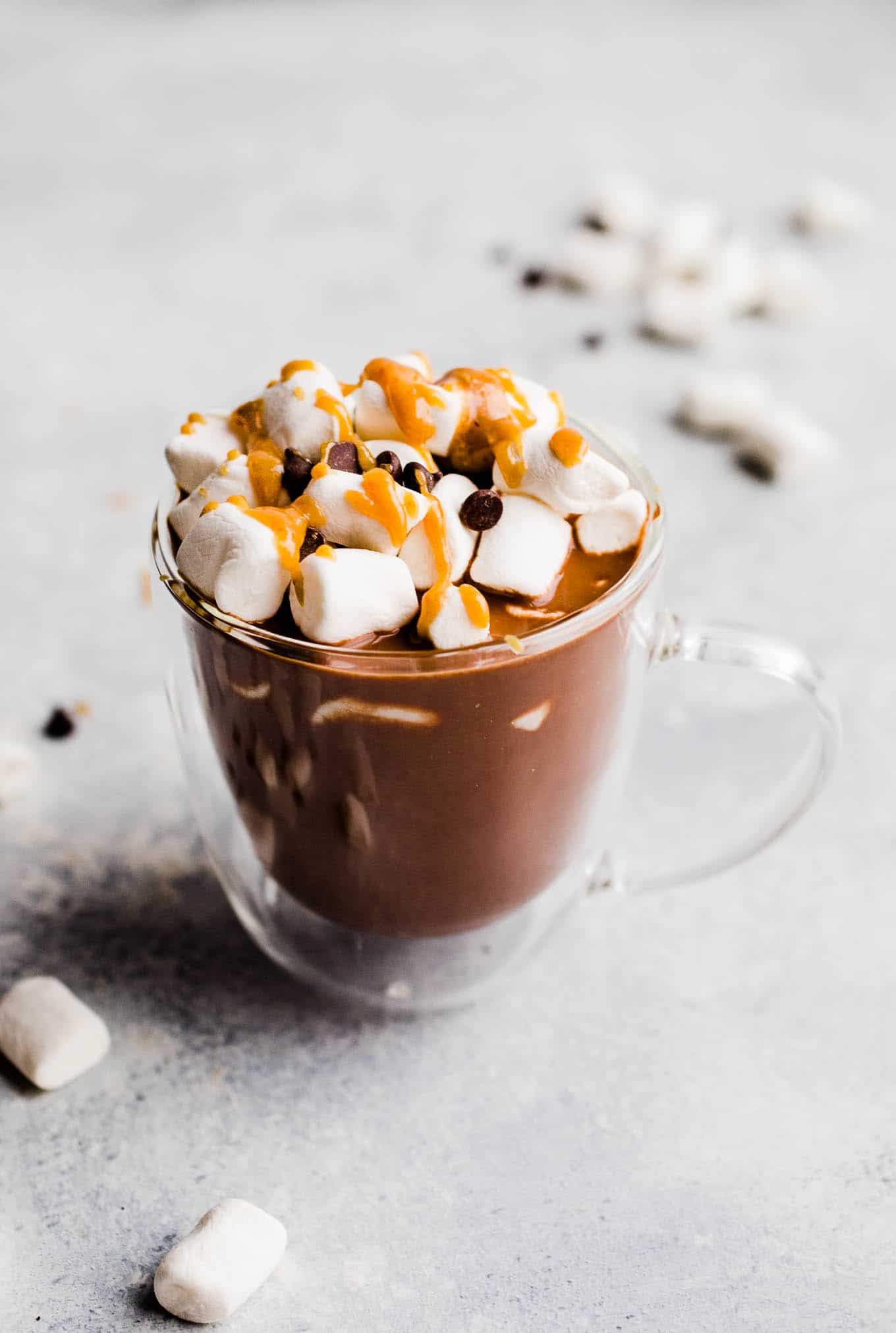 hot chocolate in glass mug with marshmallows and peanut butter sauce on top.