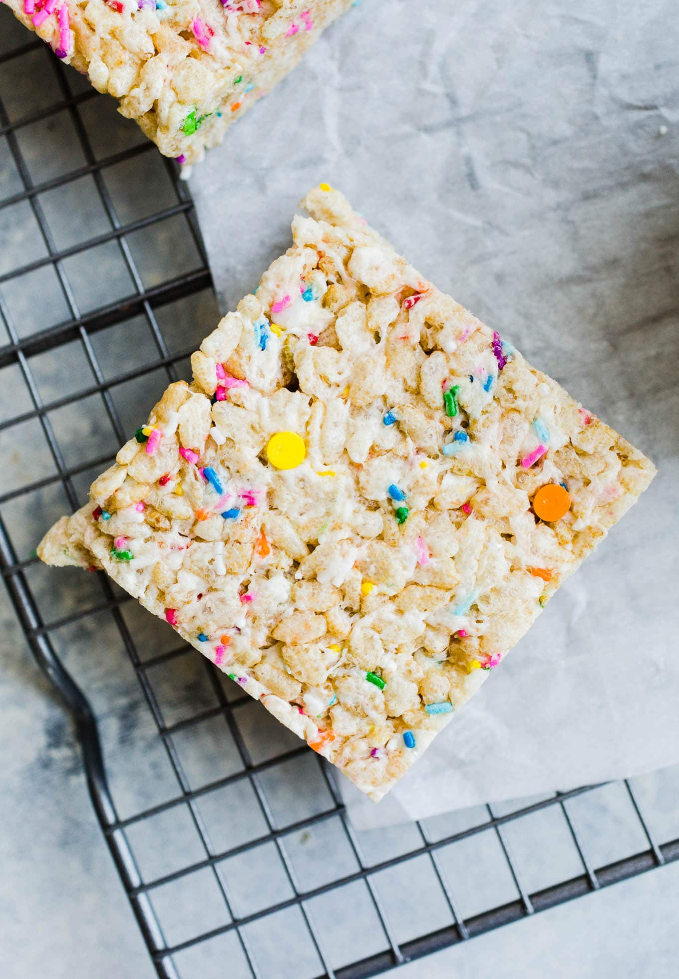 rice krispie treat square with rainbow sprinkles on wire rack