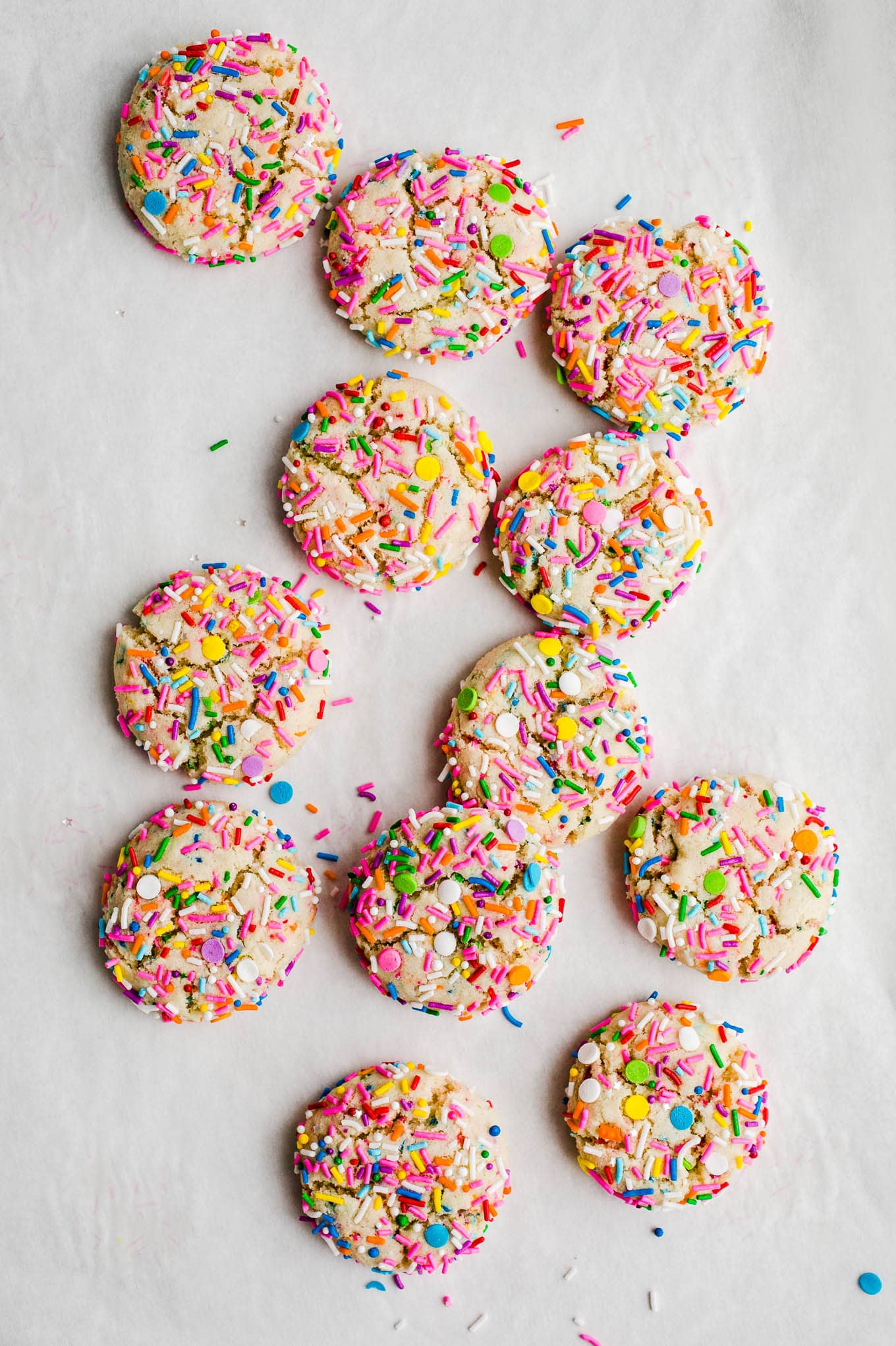 round sprinkle cookies on parchment paper
