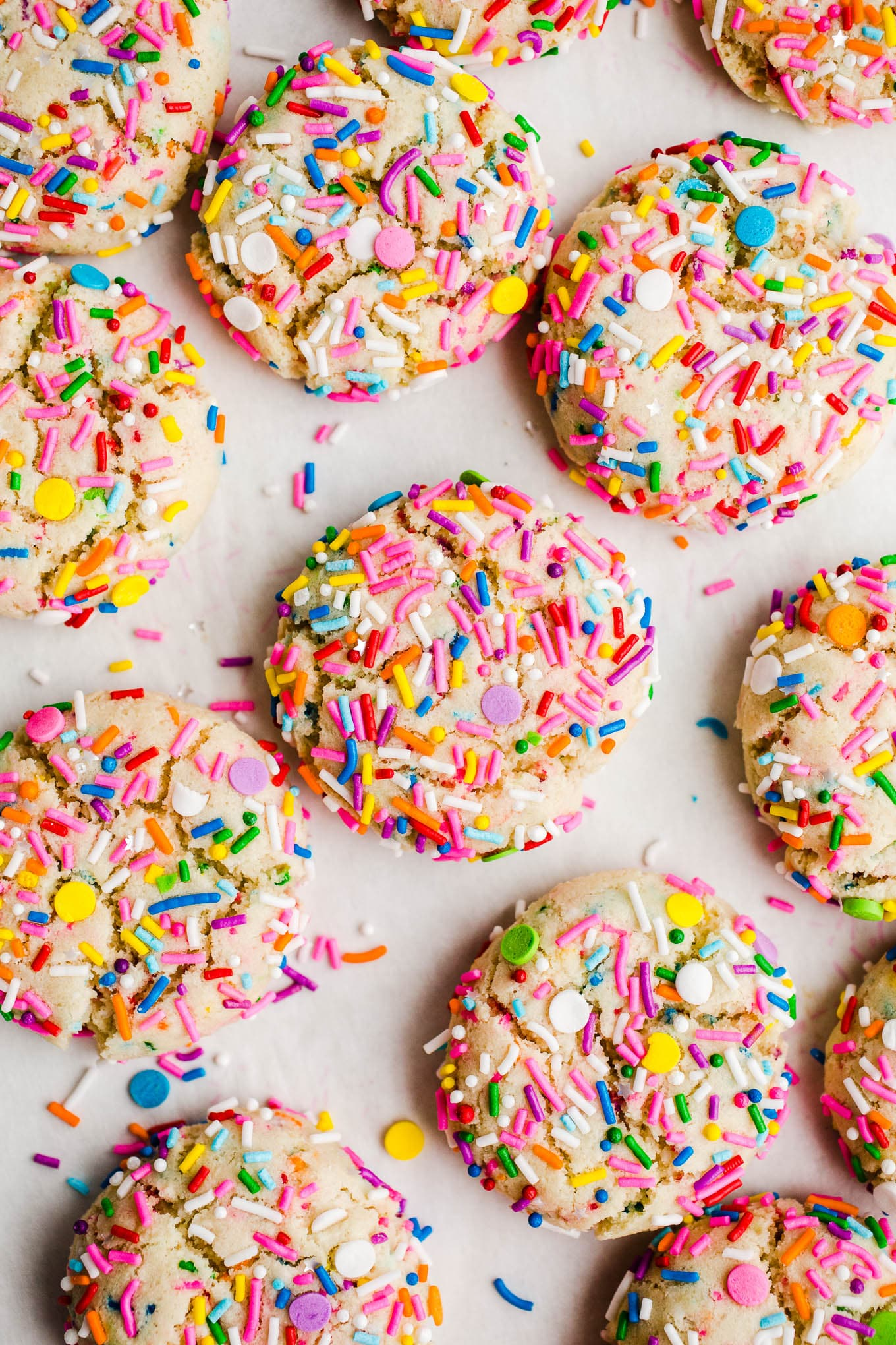 cookies with rainbow sprinkles on parchment paper