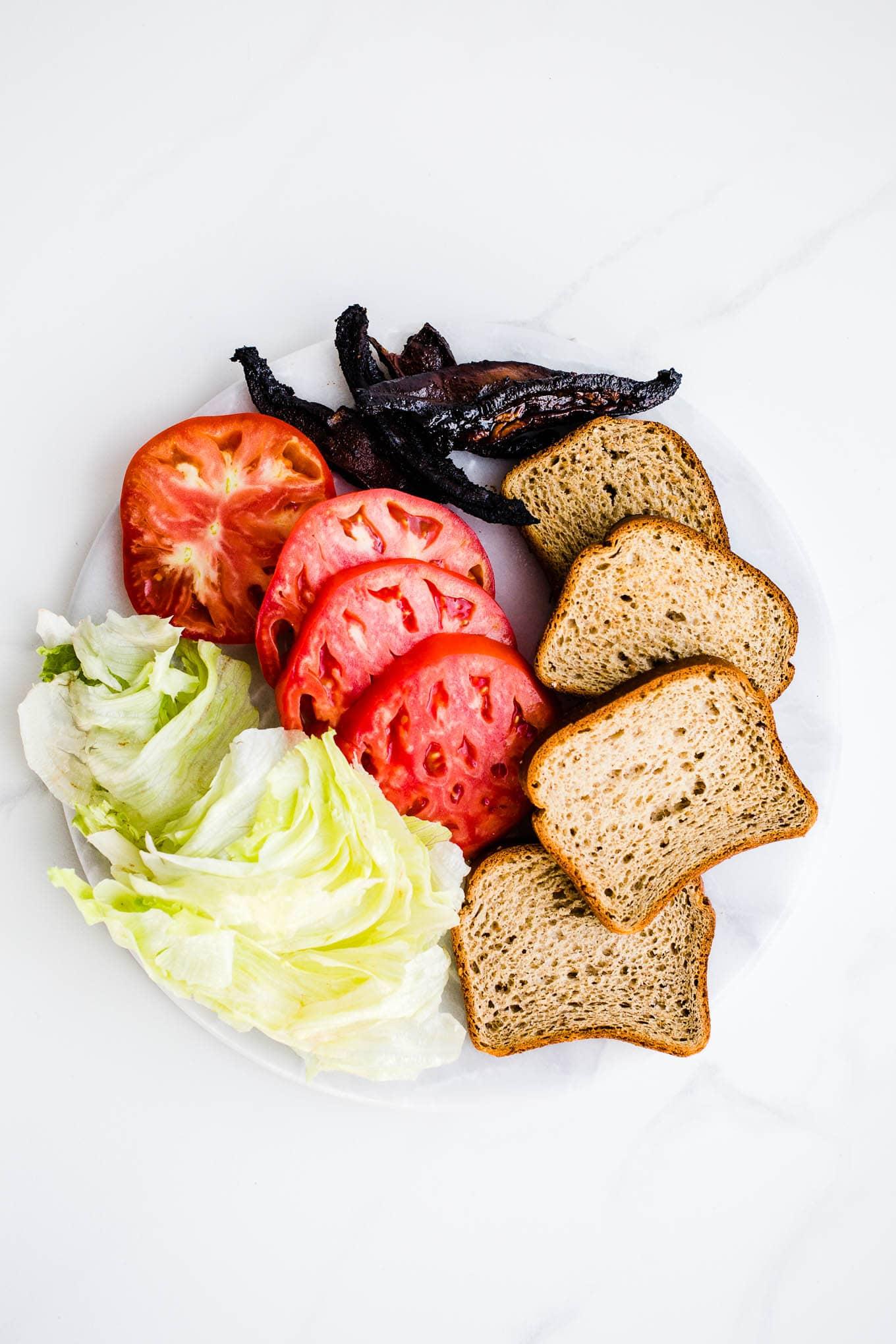 bread, mushrooms, iceberg lettuce, and tomatoes on platter